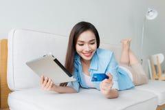Compras de la mujer en la tableta y la tarjeta de crédito que se sientan en el sof Fotos de archivo