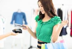 Compras de la mujer en tienda de la ropa y el pagar por smartphone Imágenes de archivo libres de regalías