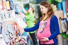 Compras de la mujer joven durante embarazo foto de archivo