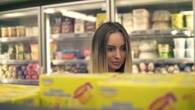 Compras de la mujer joven en colmado Mujer casual que elige la comida de estante en supermercado Situación sonriente del cliente almacen de metraje de vídeo