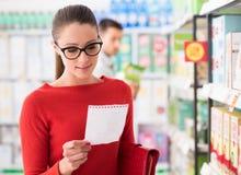 Compras de la mujer joven en el supermercado Imágenes de archivo libres de regalías