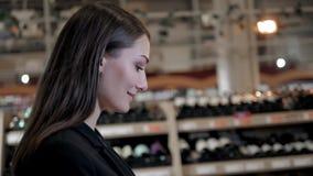 Compras de la mujer joven en el supermercado Pensando lo que ella debe comprar después, caminando con la carretilla cerca de tien almacen de metraje de vídeo