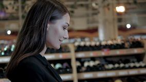 Compras de la mujer joven en el supermercado Pensando lo que ella debe comprar después, caminando con la carretilla cerca de tien