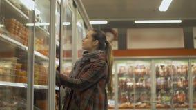 Compras de la mujer joven en el supermercado Refrigerador de la abertura para escoger la comida para arriba refrigerada almacen de metraje de vídeo