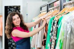 Compras de la mujer joven en grandes almacenes de la moda foto de archivo libre de regalías