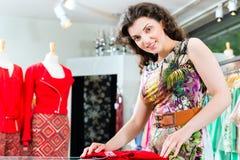 Compras de la mujer joven en grandes almacenes de la moda imagen de archivo libre de regalías