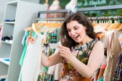 Compras de la mujer joven en grandes almacenes de la moda fotos de archivo