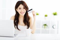 Compras de la mujer joven en línea y tarjeta de crédito de la demostración Imagenes de archivo