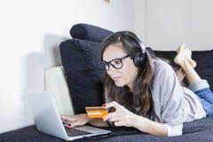 Compras de la mujer joven en línea Foto de archivo