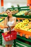 Compras de la mujer joven en un supermercado en el departamento de fruta Imagenes de archivo