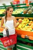 Compras de la mujer joven en un supermercado en el departamento de fruta Fotos de archivo
