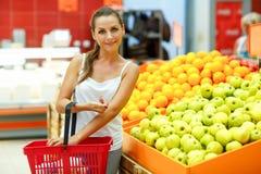 Compras de la mujer joven en un supermercado en el departamento de fruta Imagen de archivo libre de regalías