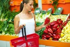 Compras de la mujer joven en un supermercado en el departamento de fruta Fotos de archivo libres de regalías