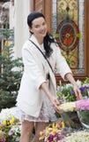 Compras de la mujer joven en una floristería del aire libre Imagenes de archivo