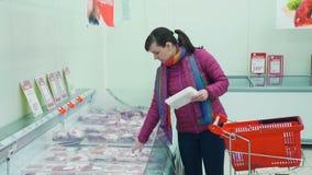 Compras de la mujer joven para la carne en un supermercado almacen de video