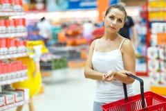Compras de la mujer joven para el cereal, bulto en un supermercado del ultramarinos Foto de archivo