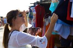 Compras de la mujer joven para la ropa en un mercado de domingo en España Imagen de archivo