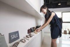 Compras de la mujer joven para los accesorios en la tienda Imagen de archivo libre de regalías