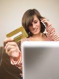 Compras de la mujer joven vía el teléfono Foto de archivo libre de regalías