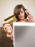 Compras de la mujer joven vía el teléfono Fotos de archivo