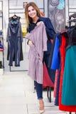 Compras de la mujer joven y mirada de un poco de ropa en una tienda Foto de archivo libre de regalías