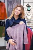 Compras de la mujer joven y mirada de un poco de ropa en una tienda Fotos de archivo libres de regalías