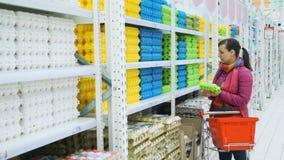 Compras de la mujer para los huevos en un supermercado almacen de metraje de vídeo