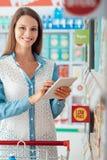 Compras de la mujer y usar una tableta imagenes de archivo