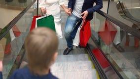 Compras de la Navidad de la familia Los padres con el niño van en la escalera móvil con los paquetes de regalos paquetes multicol almacen de metraje de vídeo