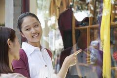 Compras de la ventana de dos mujeres jovenes Foto de archivo libre de regalías