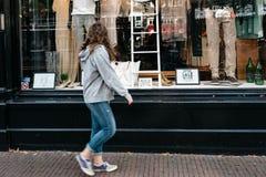 Compras de la ventana de la mujer que van en la tienda de la moda Fotos de archivo