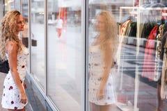 Compras de la ventana - muchacha rubia rizada atractiva que se coloca en frente Imagenes de archivo