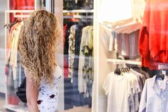 Compras de la ventana - muchacha rubia rizada atractiva que se coloca en frente fotografía de archivo