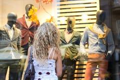 Compras de la ventana - muchacha rubia rizada atractiva que se coloca en frente Imagen de archivo libre de regalías