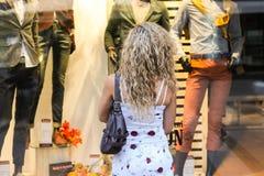 Compras de la ventana - muchacha rubia rizada atractiva que se coloca en frente Fotos de archivo