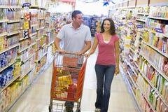 Compras de los pares en pasillo del supermercado Imagen de archivo libre de regalías
