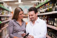 Compras de los pares para el vino en el supermercado Imagen de archivo libre de regalías