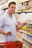 Compras de tienda de comestibles del hombre joven Imágenes de archivo libres de regalías