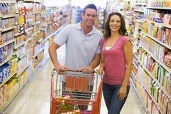 Compras de tienda de comestibles jovenes de los pares foto de archivo