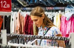 Compras del adolescente para la ropa dentro de la tienda de ropa Imagenes de archivo