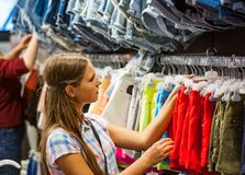 Compras del adolescente para la ropa dentro de la tienda de ropa Imágenes de archivo libres de regalías