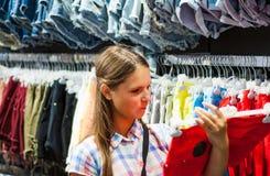 Compras del adolescente para la ropa dentro de la tienda de ropa Imagen de archivo libre de regalías