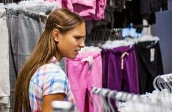 Compras del adolescente para la ropa dentro de la tienda de ropa Foto de archivo libre de regalías