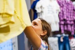 Compras del adolescente para la ropa dentro de la tienda de ropa Fotografía de archivo libre de regalías
