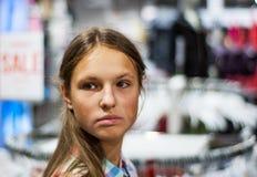 Compras del adolescente para la ropa dentro de la tienda de ropa Foto de archivo