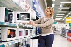 Compras del ama de casa de la mujer para el horno de microondas imagen de archivo