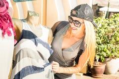 Compras del blogger de la moda de la mujer joven con música en el mercado de pulgas foto de archivo
