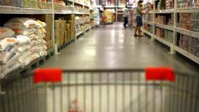 Compras del cliente en el supermercado con la carretilla almacen de metraje de vídeo