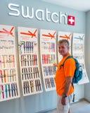 Compras del hombre en la tienda de Swatch foto de archivo libre de regalías