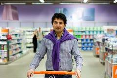 Compras del hombre en una sección de los bienes de consumo Foto de archivo libre de regalías